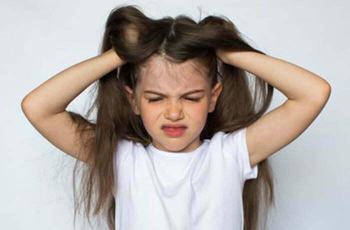 niña enfadada rascándose la cabeza