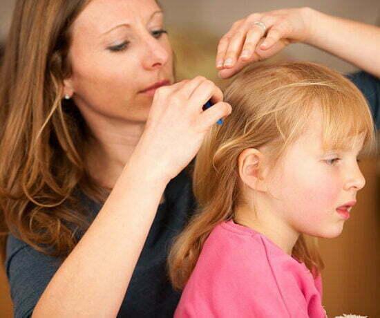 madre peinando liendres hija
