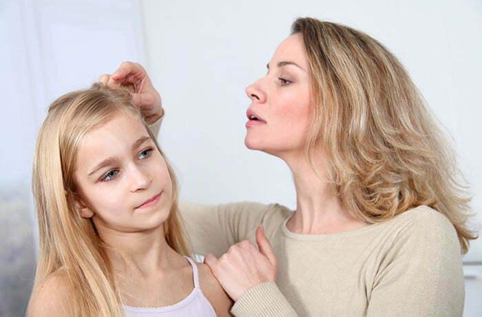madre buscando piojos en hija
